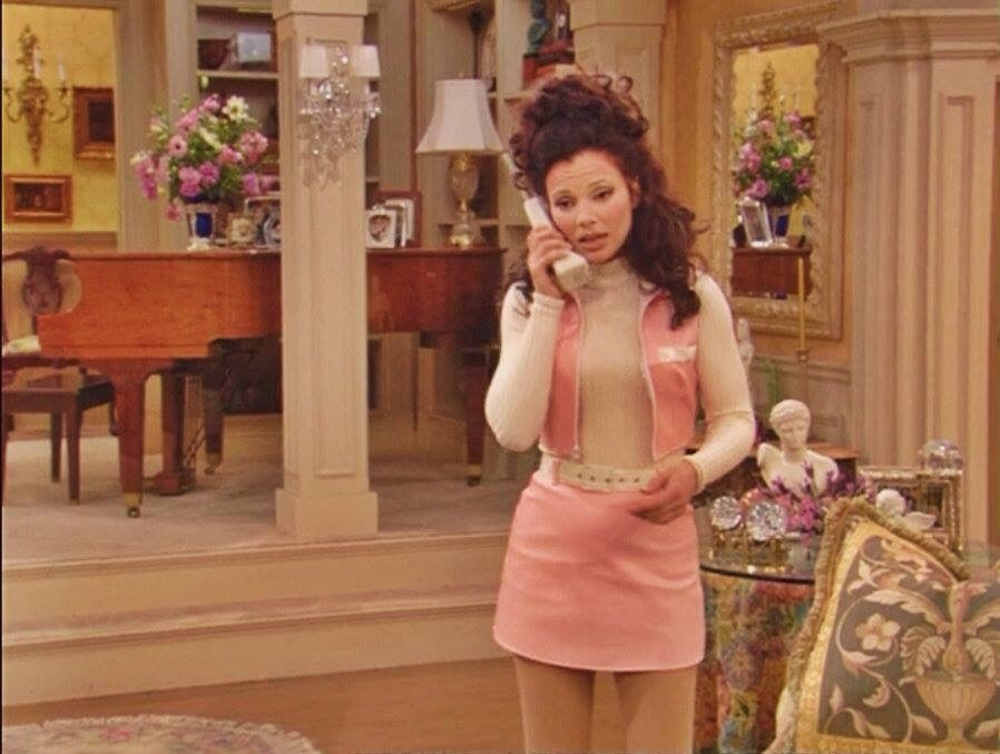 Fran is talking on the phone in an opulent room with a grand piano and vase of flowers in the background.