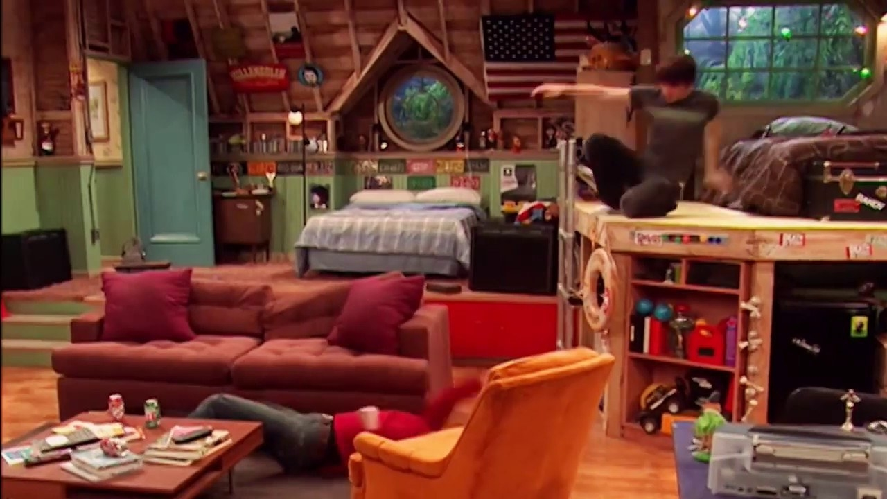 Josh is laying on the floor near a couch and Drake is jumping down from his platform bed to help him.
