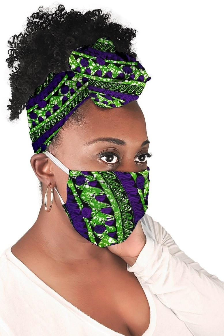 Model in green and purple patterned face mask and matching hair wrap