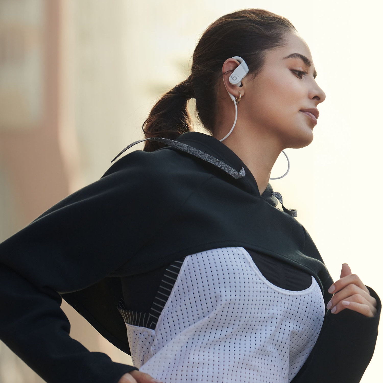 person wearing white powerbeats headphones while running