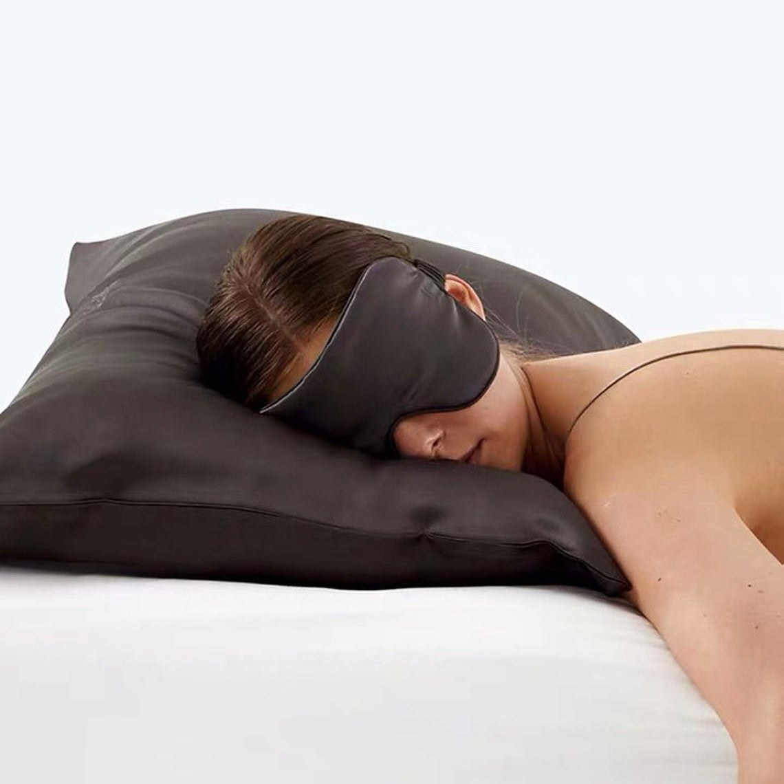 Model asleep on silk pillow with mask
