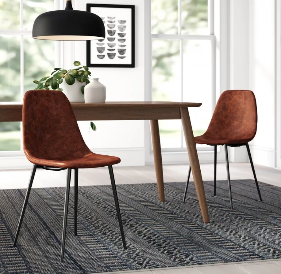 Cooper brown upholstered chairs with black legs around wooden dining table