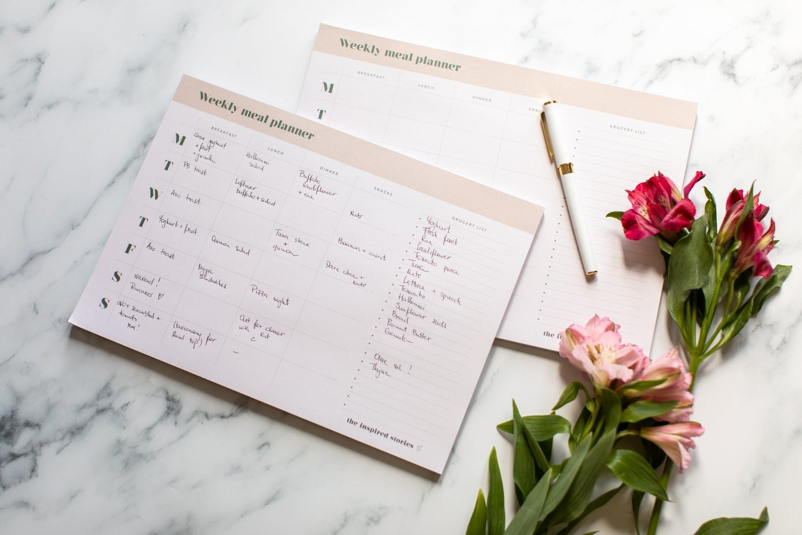 Weekly meal planner on marble table next to flowers