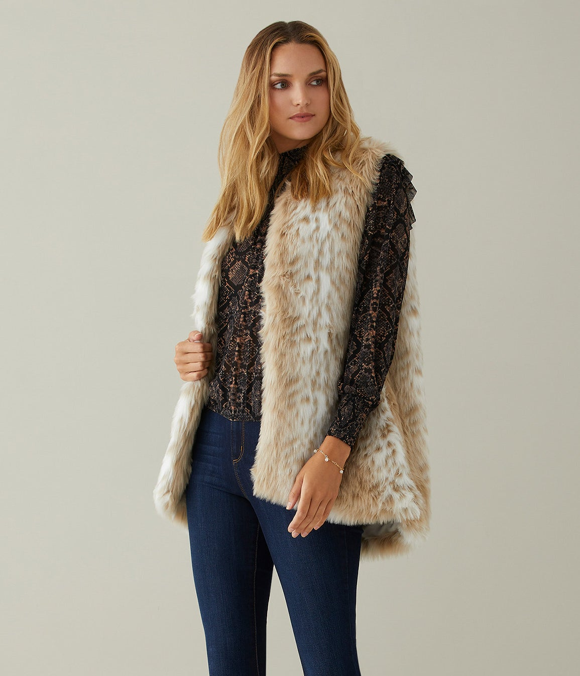 model wearing a light-colored faux fur vest and blue jeans