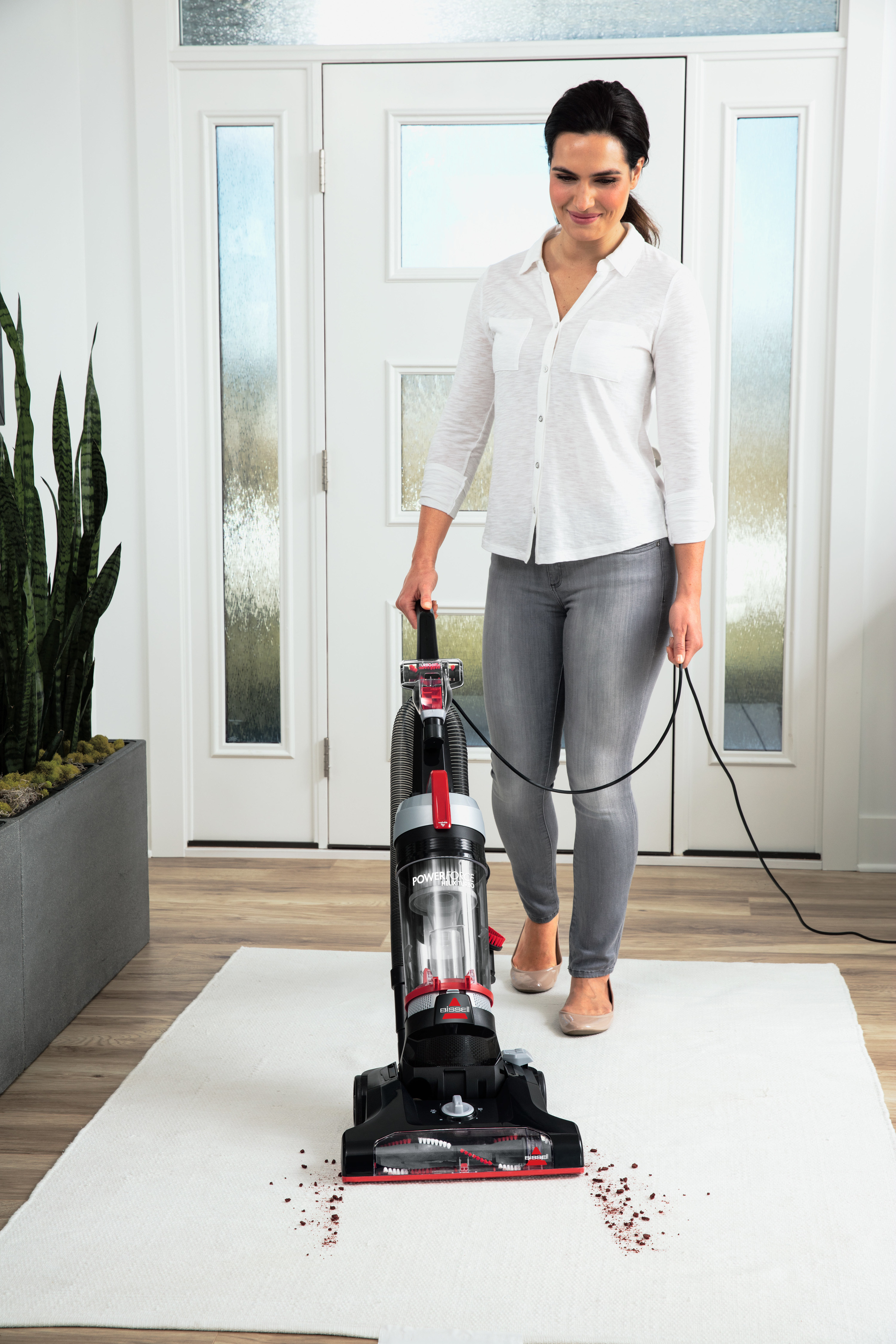 person using a bissell vacuum to clean up dog food