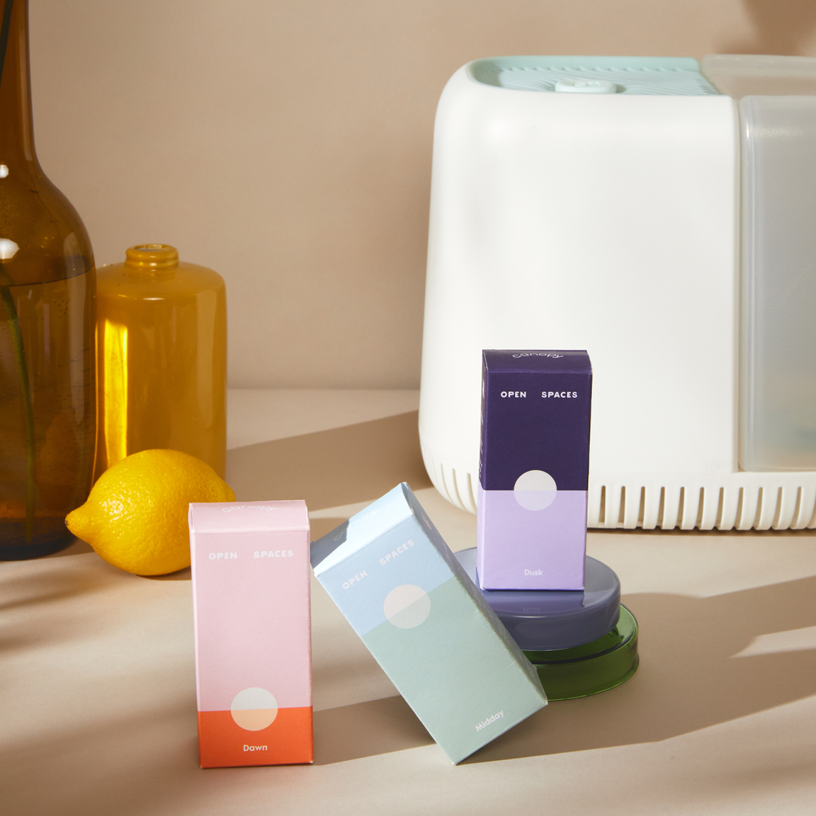 the white rectangle humidifier with three small fragrance boxes in pink, blue, and purple sitting in front of it
