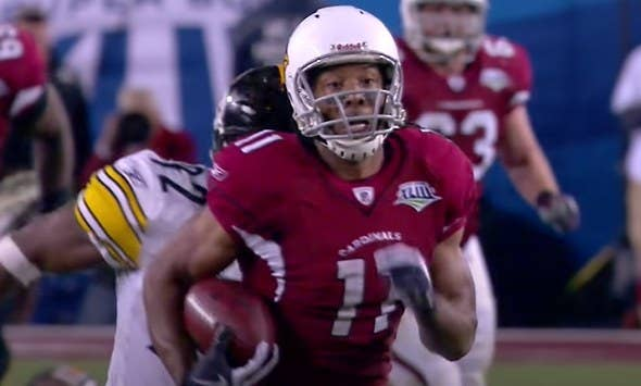 Larry Fitzgerald running with football.