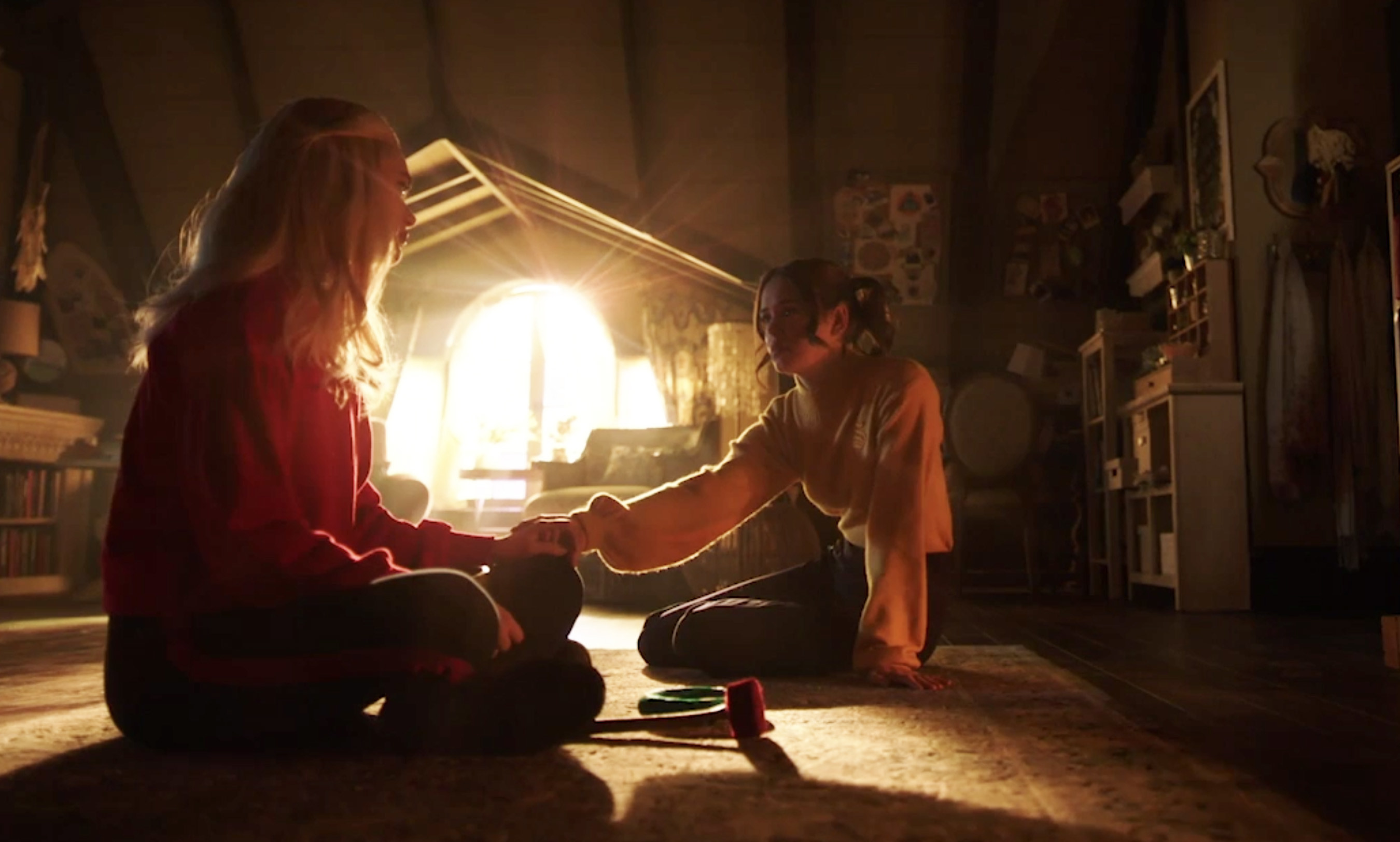 Lizzie and Josie holding hands in their bedroom