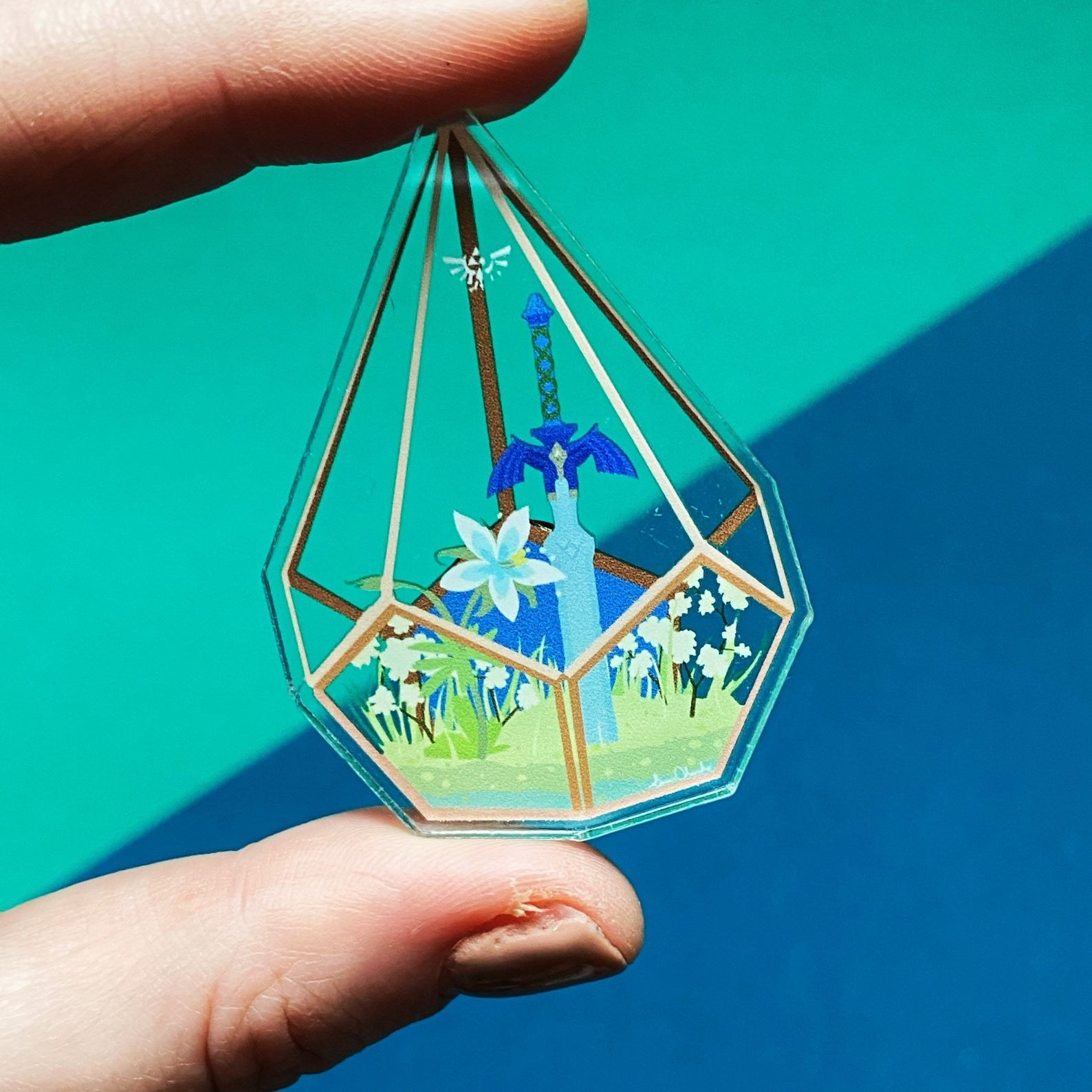 a pin of a terrarium with flowers and a sword inside