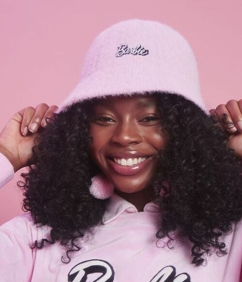 Model wears the pink bucket hat with black and pink barbie embroidery