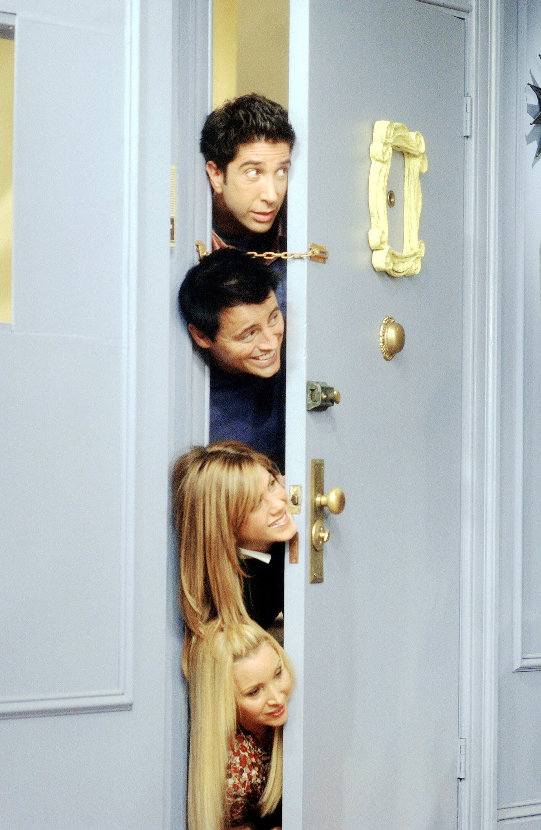 The Friends with their heads over each other in a doorway on Friends