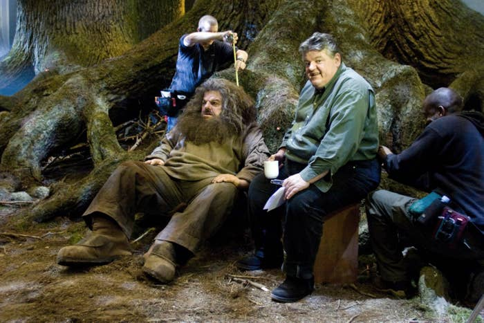 the actor for Hagrid, Robbie Coltrane, posing next to a fake human-sized doll Hagrid