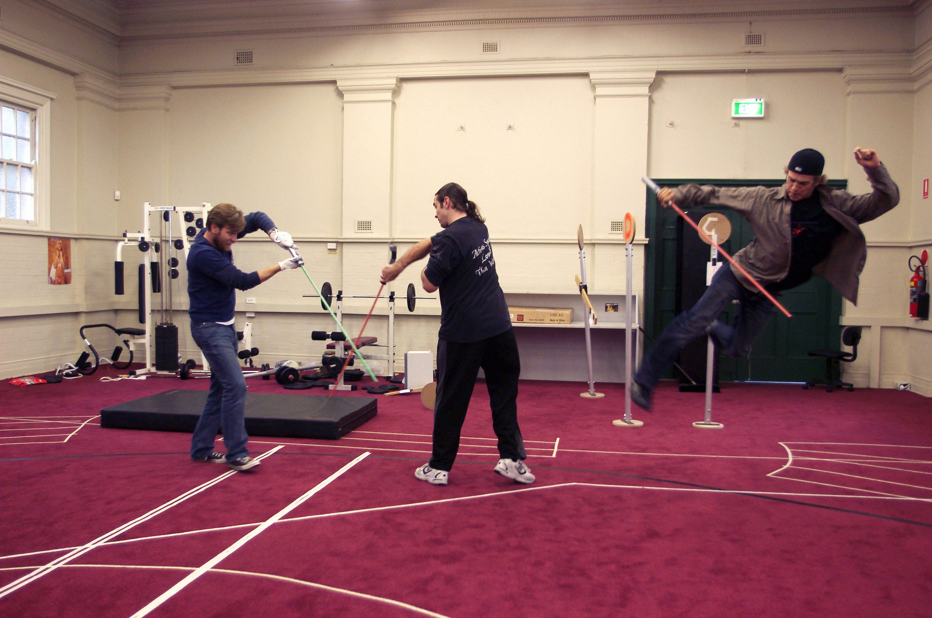 Ewan McGregor and a stunt double practicing a light saber fight with sticks in a gym as Hayden jumps and does a kick while holding a stick