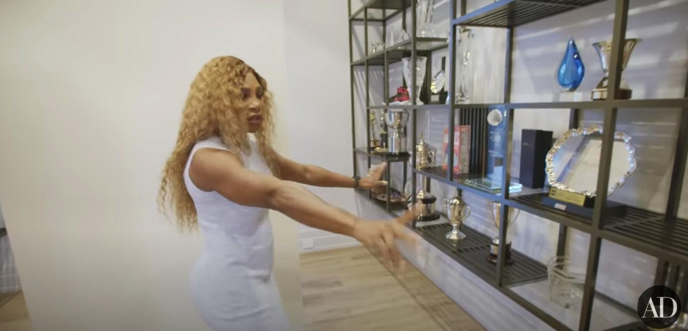 Serena Williams points at her trophy shelves in her trophy room