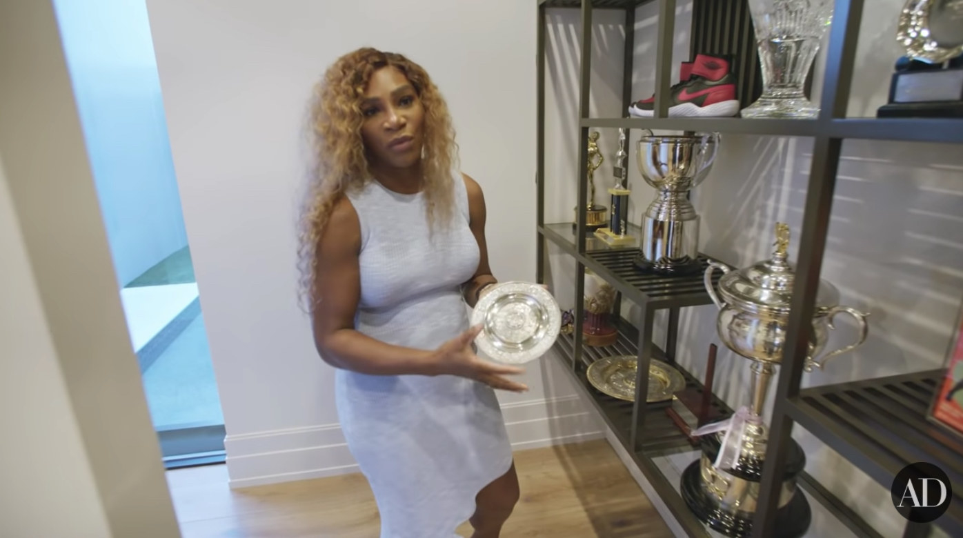 Serena Williams holds up the smaller of her two Wimbledon trophies