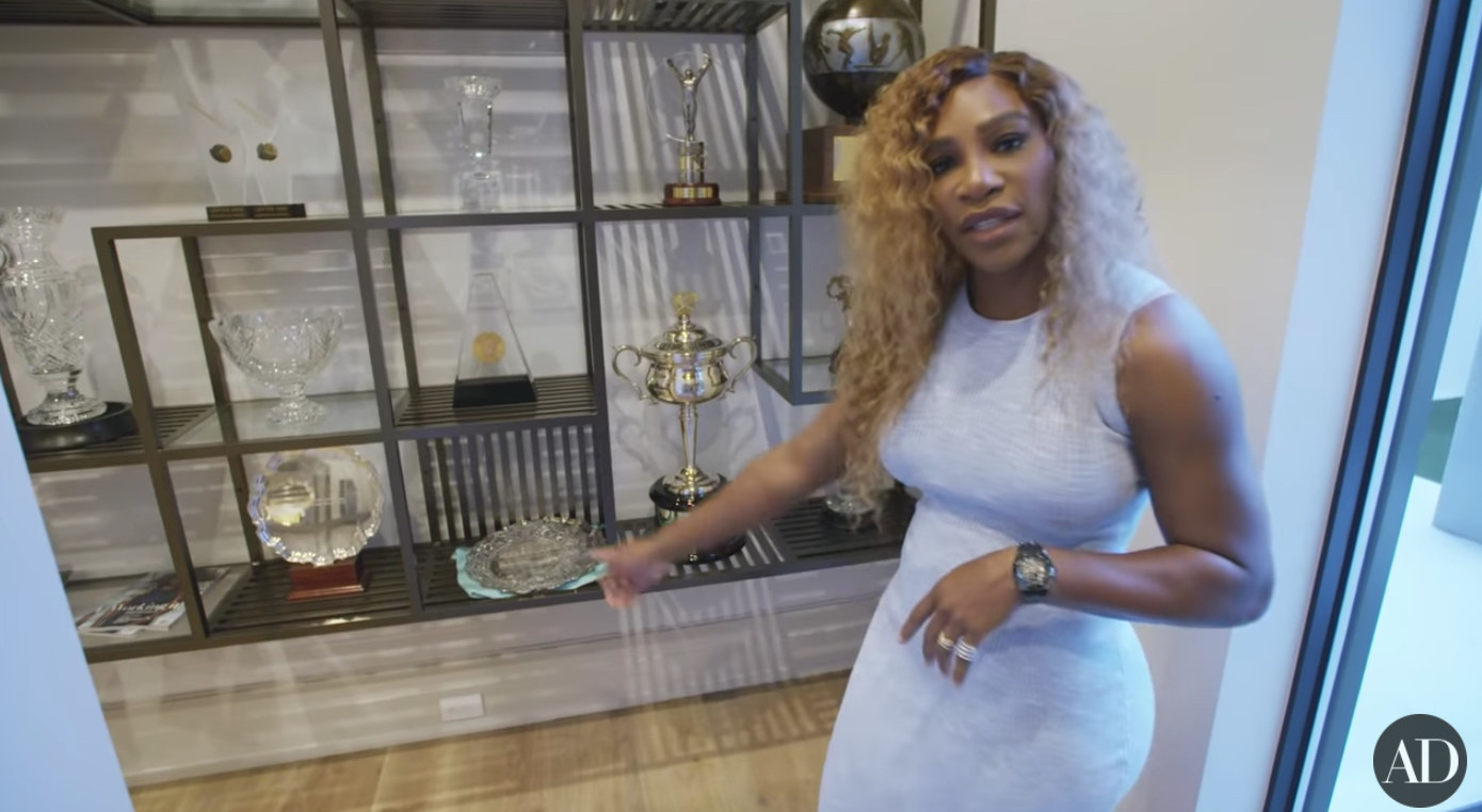 Serena Williams points to a second-place trophy in her trophy room