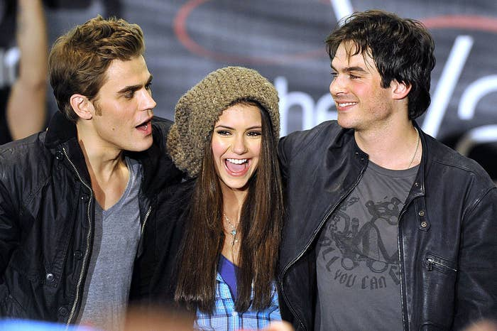 Paul Wesley, Nina Dubrev, and Ian Somerhalder smile with their arms around each other at 'The Vampire Diaries' Hot Topic tour in California