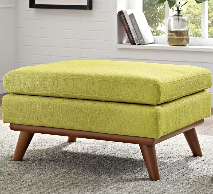 Green cushioned ottoman with wooden legs