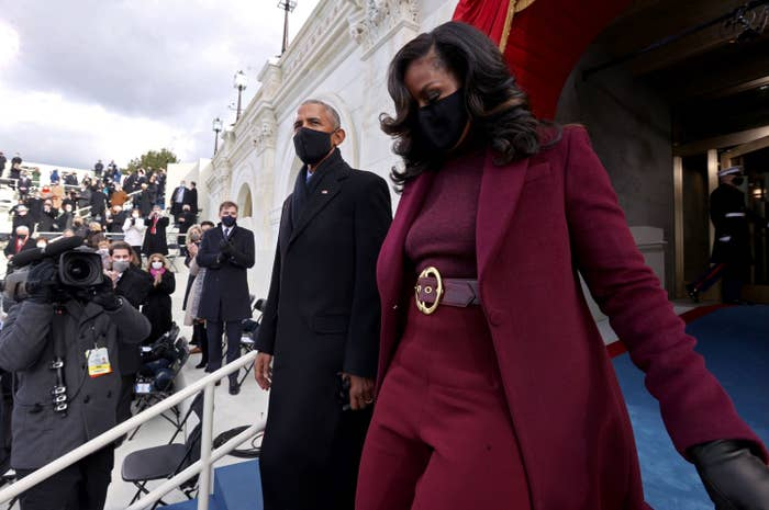 Michelle, wearing a knitted top with matching pants, belt, and long coat descends the stairs at President Joe Biden's inauguration along with Barack Obama
