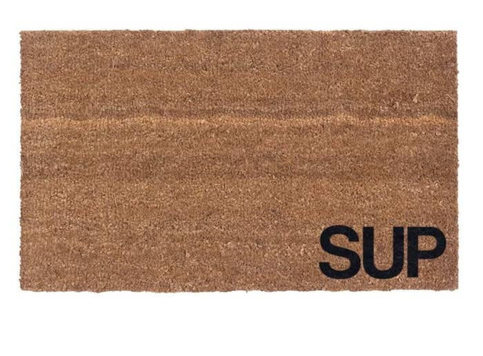 """Brown doormat with the word """"SUP"""" in black writing lower righthand corner"""