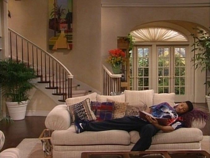 Will is laying on a white couch with colorful pillows. A curved staircase and French doors are in the background.