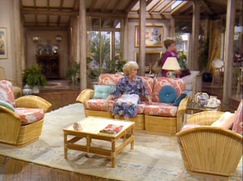 A spacious living room with wicker furniture that has pink cushions. Rose is sitting on the couch and Blanche is walking in the background.