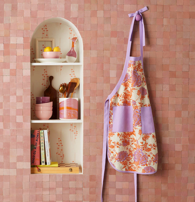 abstract marble utensil holder on a shelf next to bowls, and an apron hanging on the wall