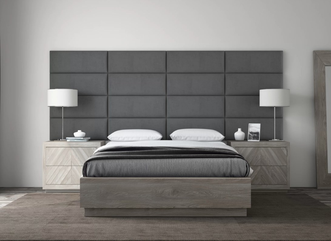 Gray headboard behind gray bed, and lamp and end table on both sides of bed