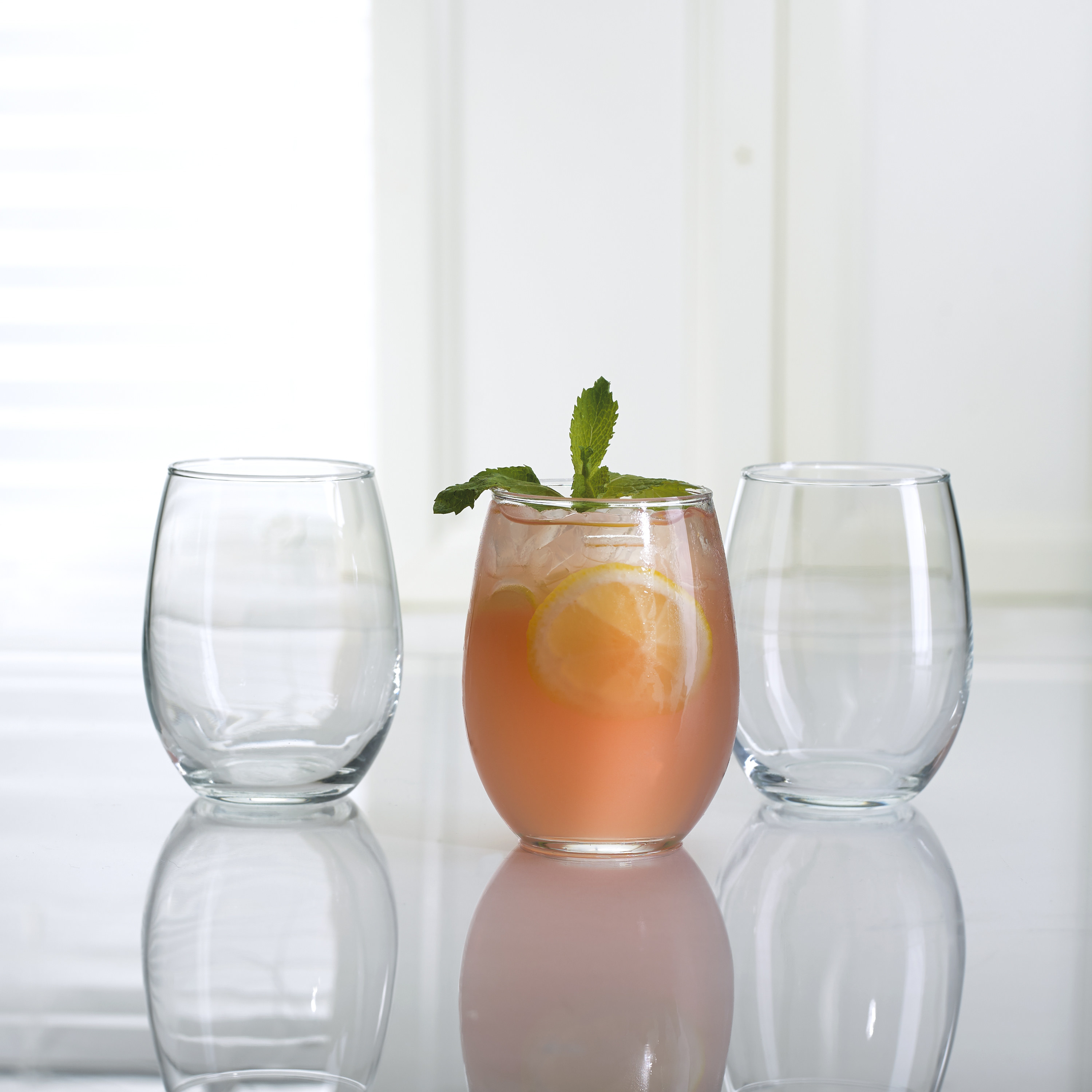 three stemless wine glasses on a table, one with a pink beverage