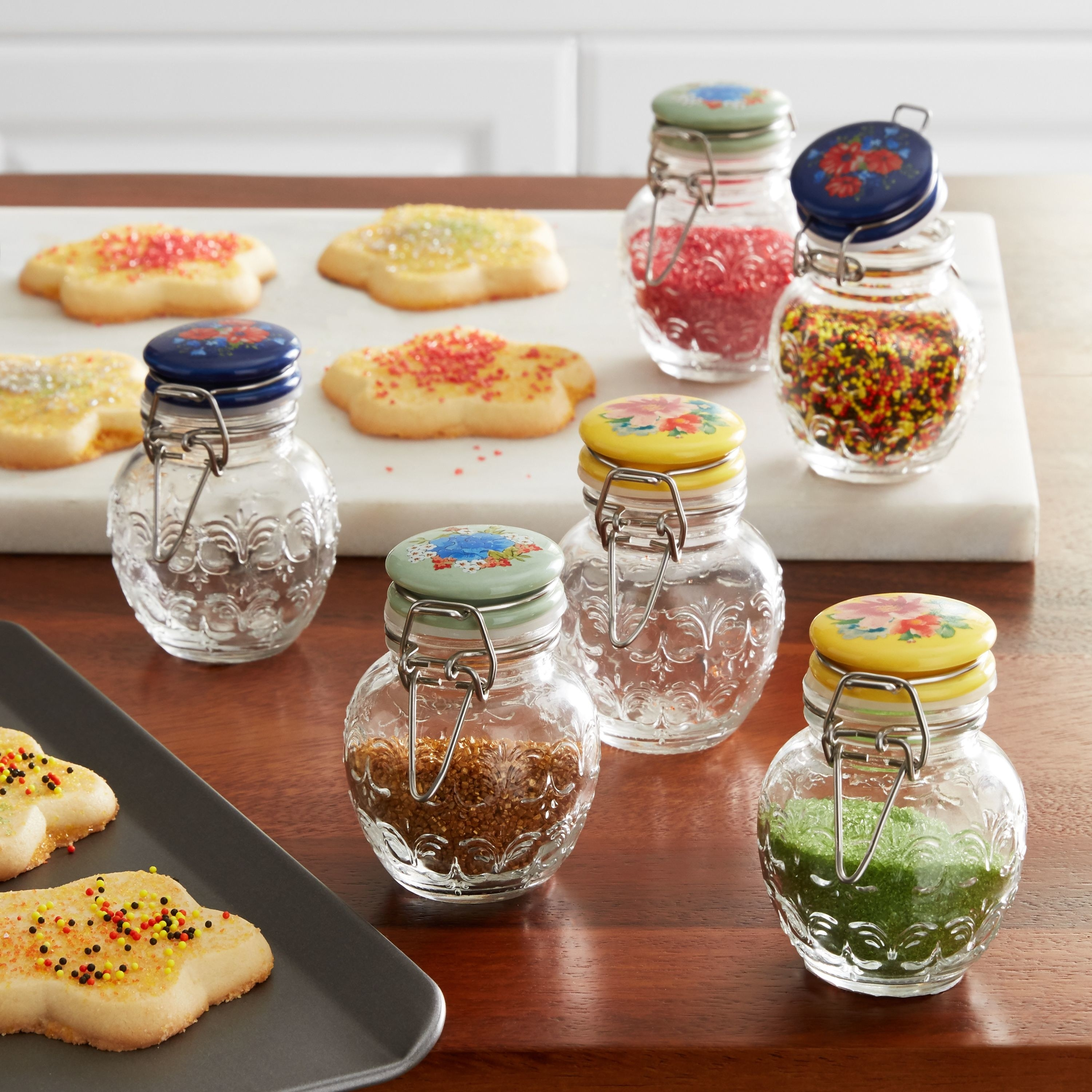 small clear jars with floral tops and filled with colored sprinkles on a table next to sugar cookies