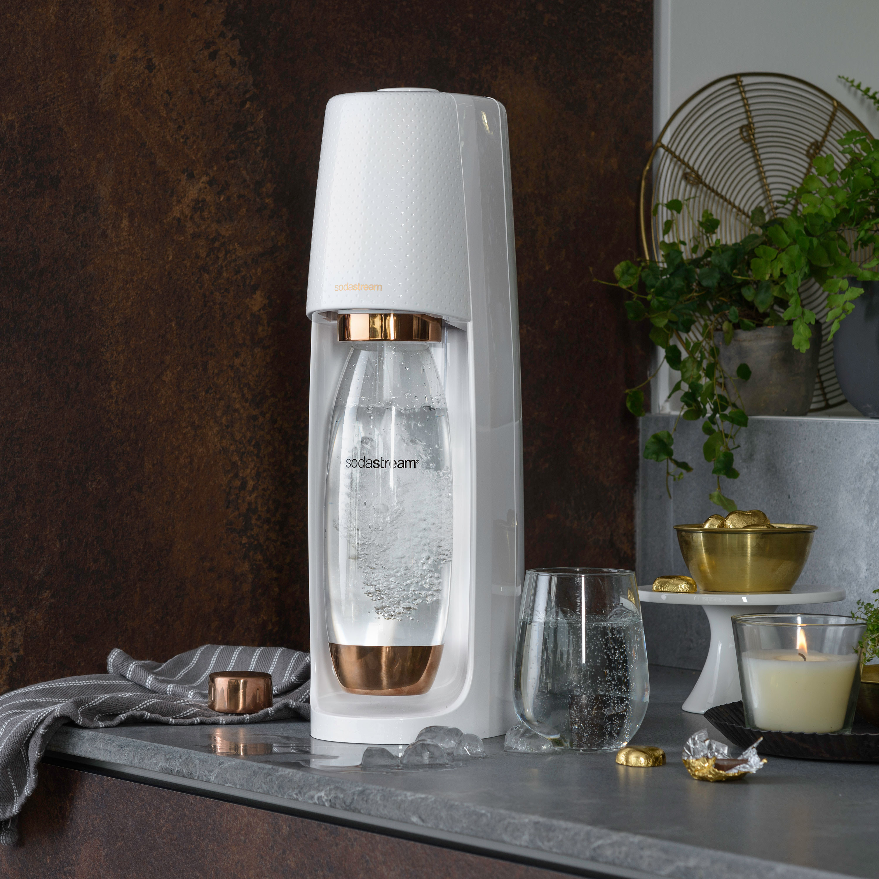 white and rose gold soda stream machine on a counter next to a glass of carbonated water