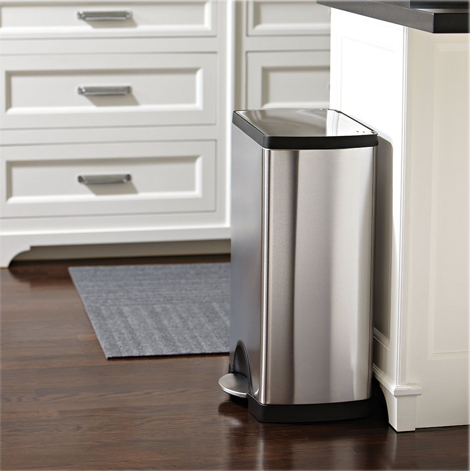 stainless steep step trashcan sitting next to a white kitchen counter