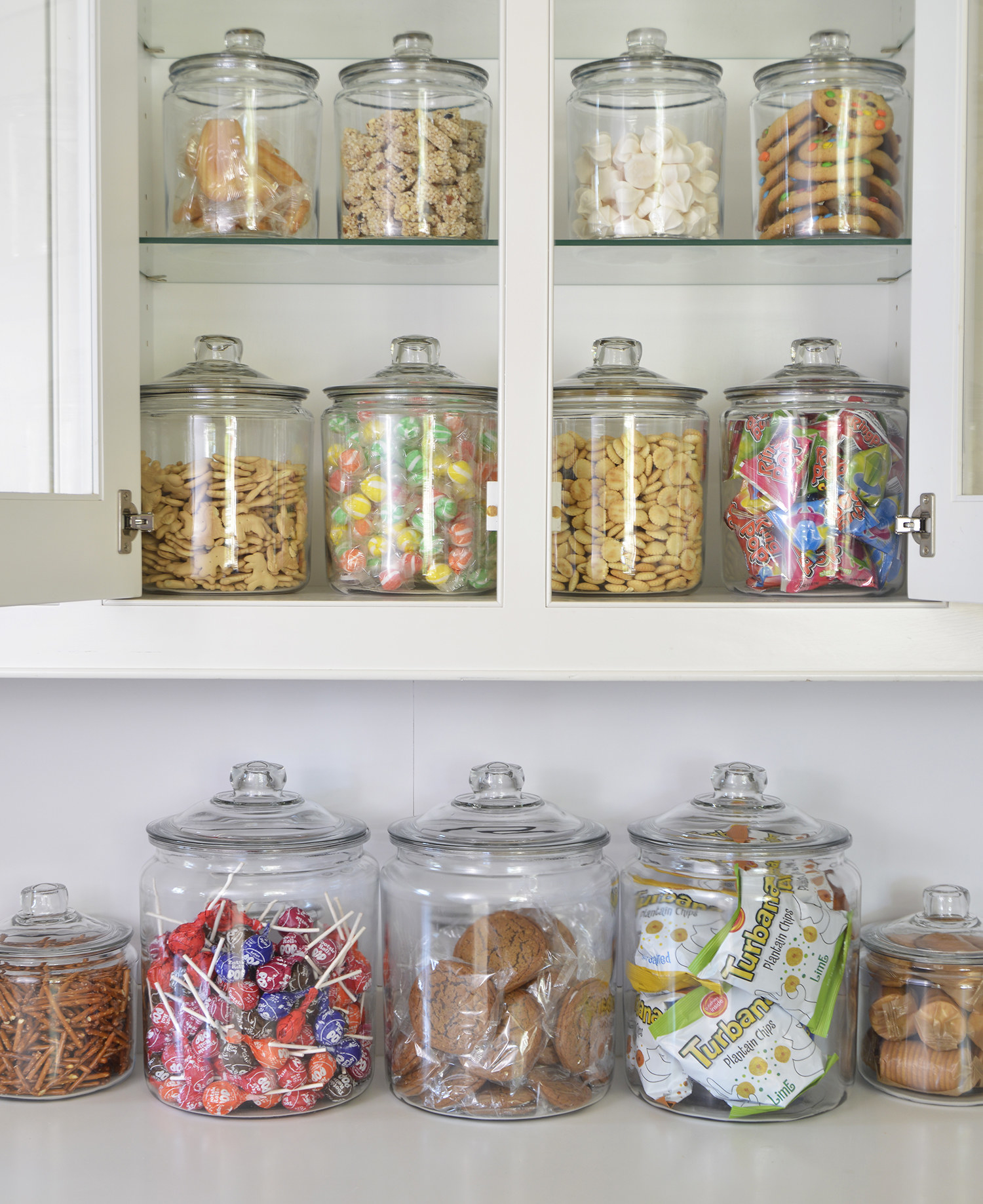 glass jars full of candies and snacks sitting on shelves