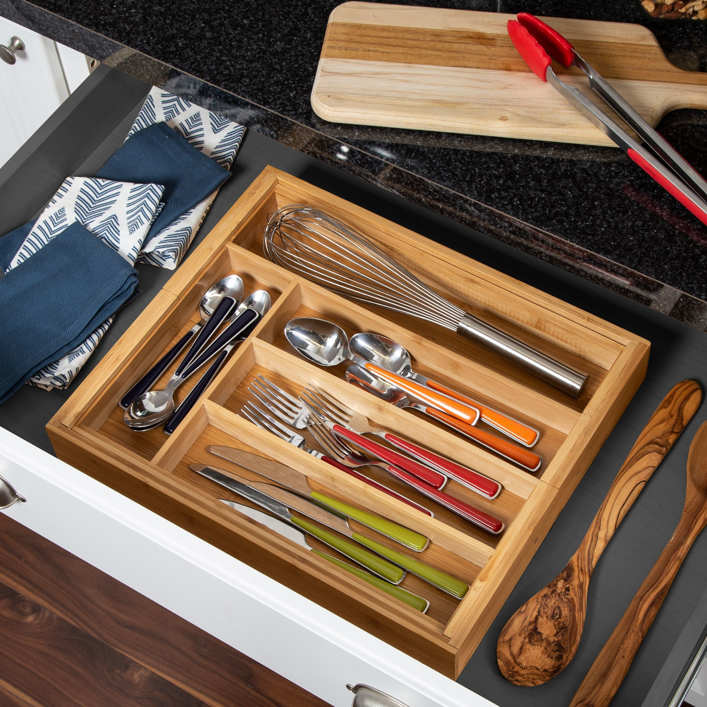 bamboo kitchen drawer organizer inside a drawer with silverware and utensils inside