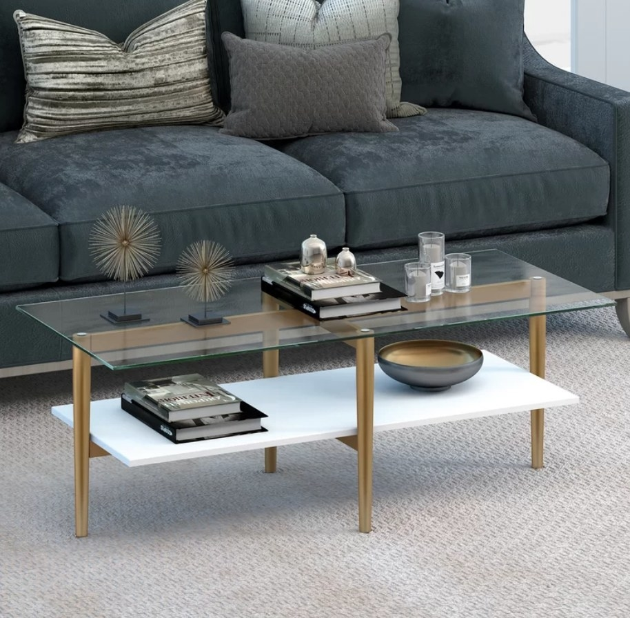 Clear glass coffee table with white bottom shelf and gold legs