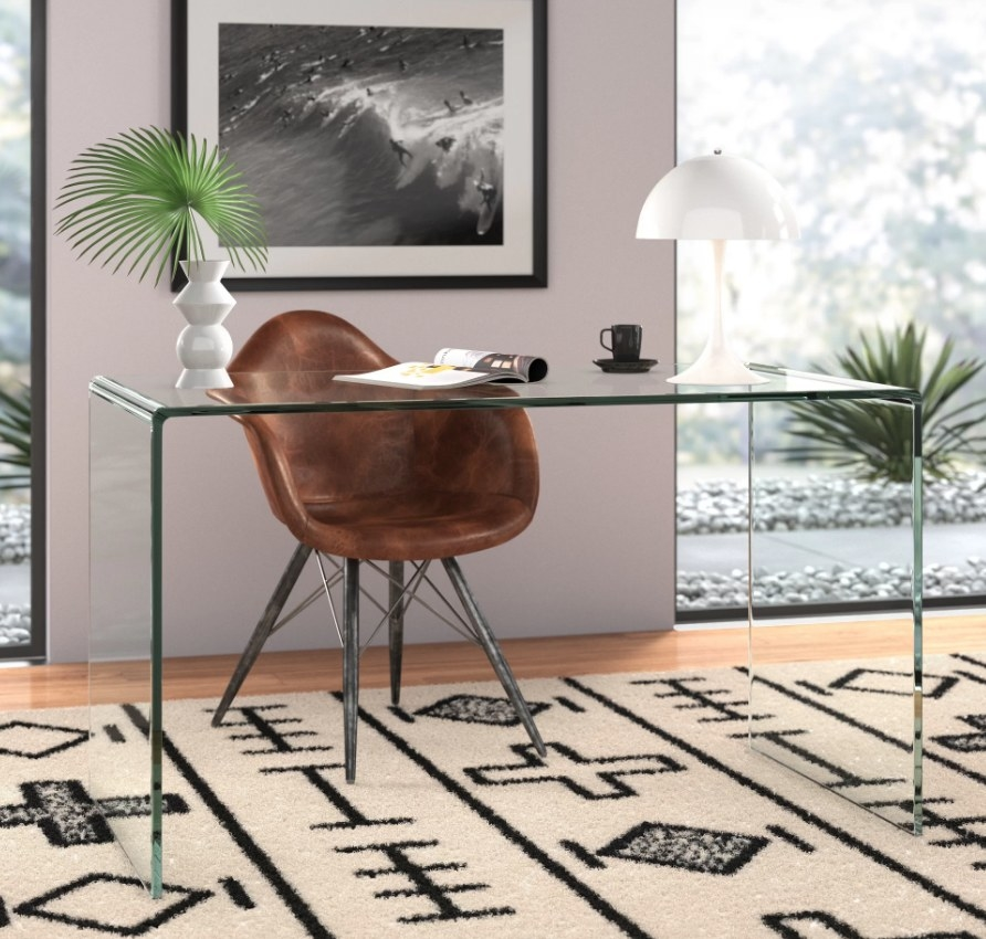 Clear desk on ivory/black rug, with brown chair behind it, vases, books, coffee cup on top