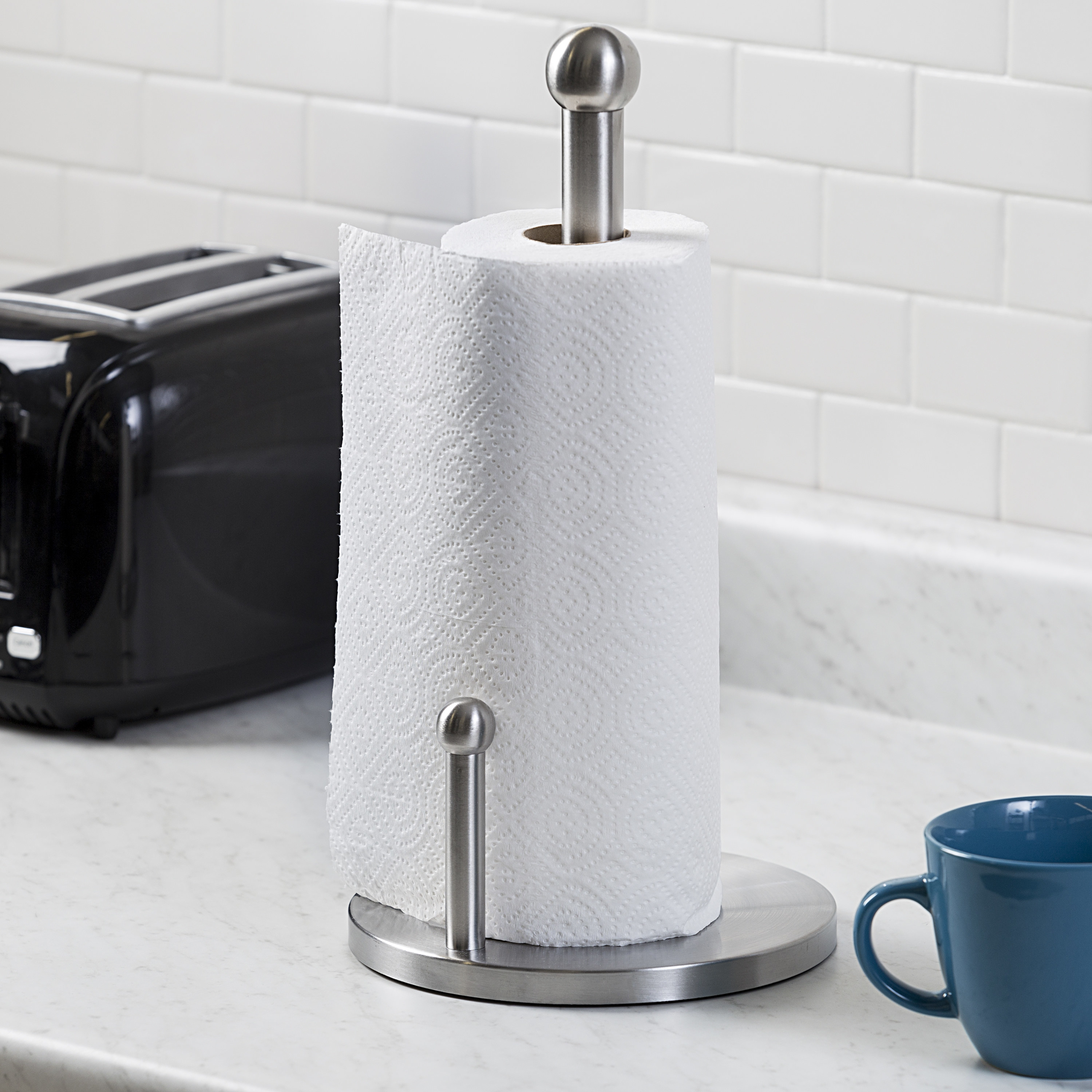 stainless steel paper towel holder with a roll of paper towels in it, sitting on a counter
