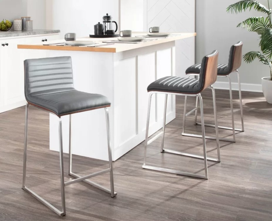 Gray upholstered bar stools with wooden back and silver legs