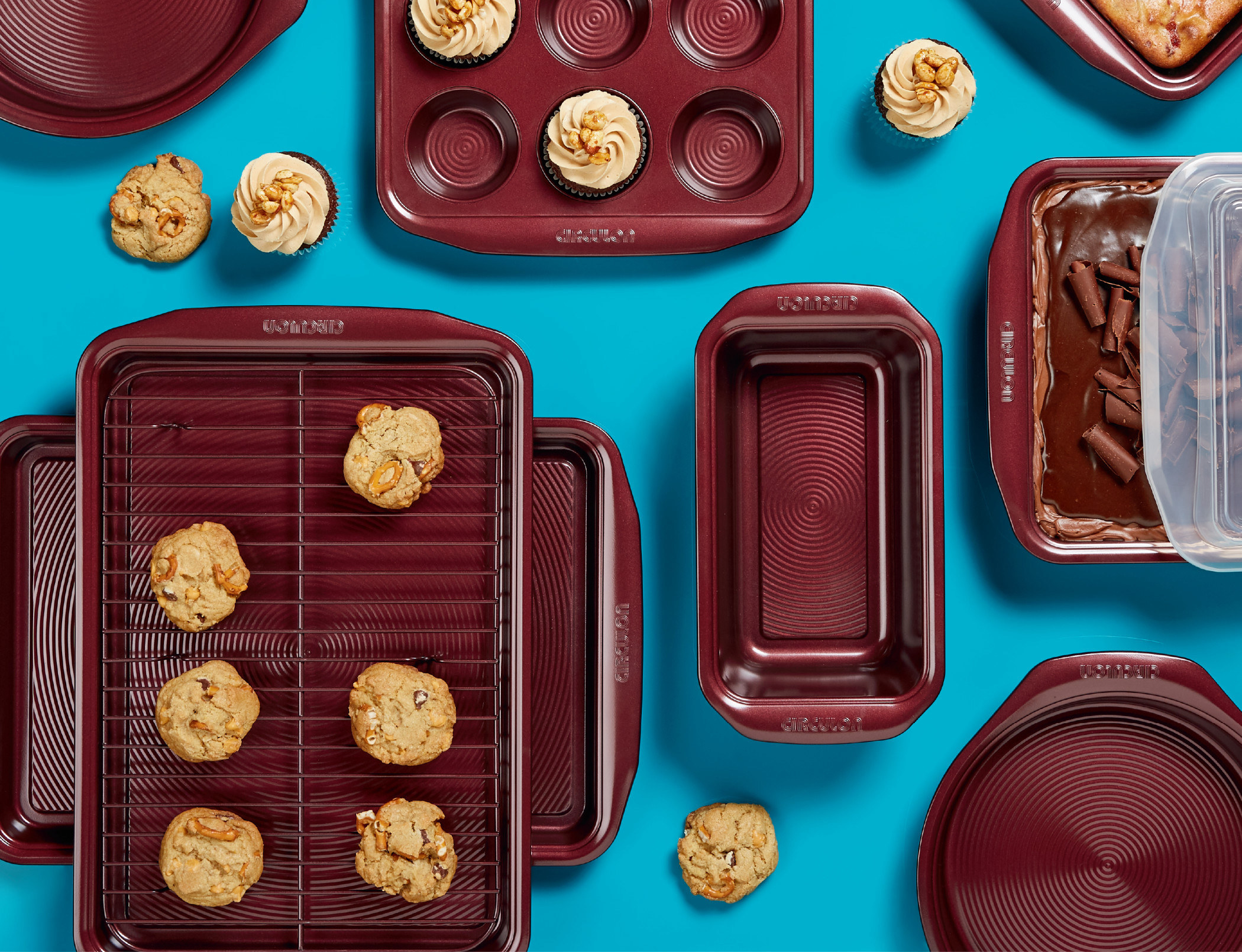 merlot colored bakeware and baked goods on a table, including muffin tin, cake pans, cookie sheet