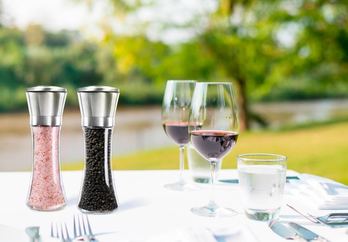 stainless steel salt and pepper shakers with glass base on a table, filled with pink salt and peppercorns