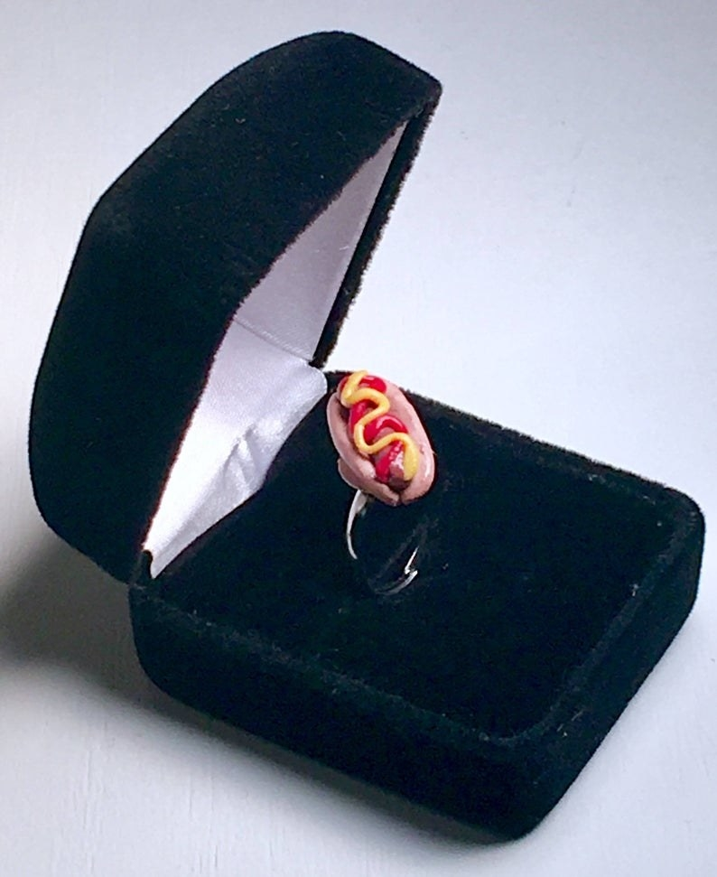 a small hot dog on a ring in a black box
