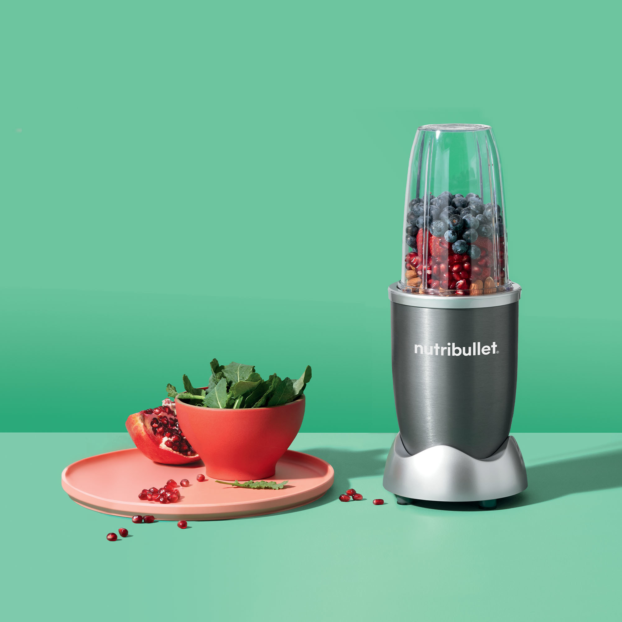 grey nutribullet with fruit inside next to a plate of vegetables and fruit on a green backdrop