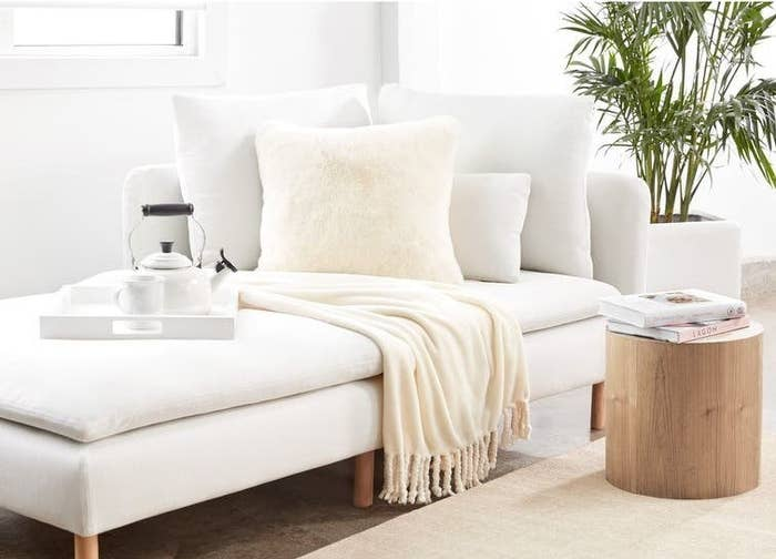 The blanket, in ivory, on a white chaise lounge