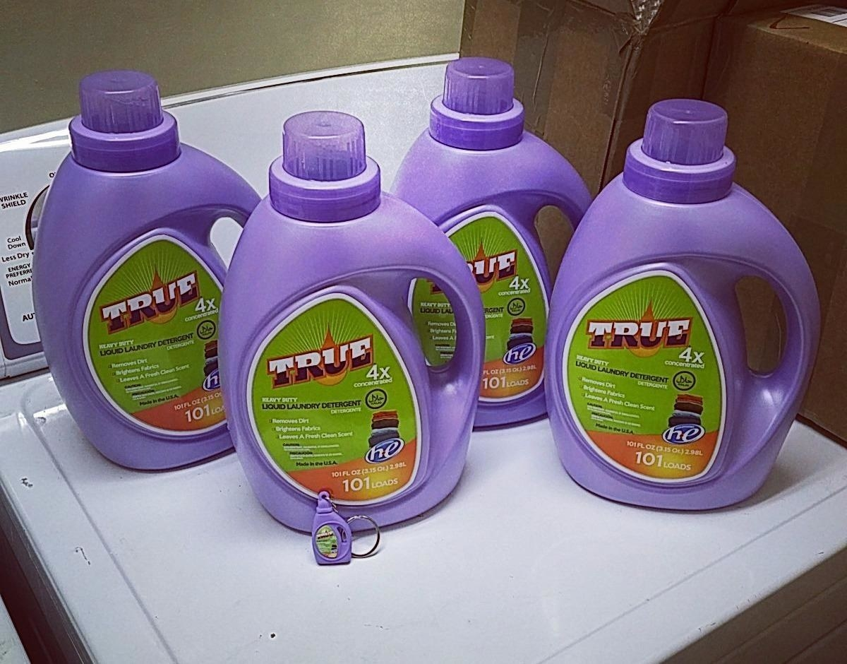 Four bottles of True laundry detergent on top of washing machine