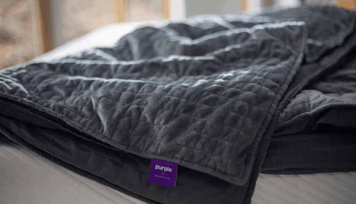 the dark grey blanket with quilted side up on a bed