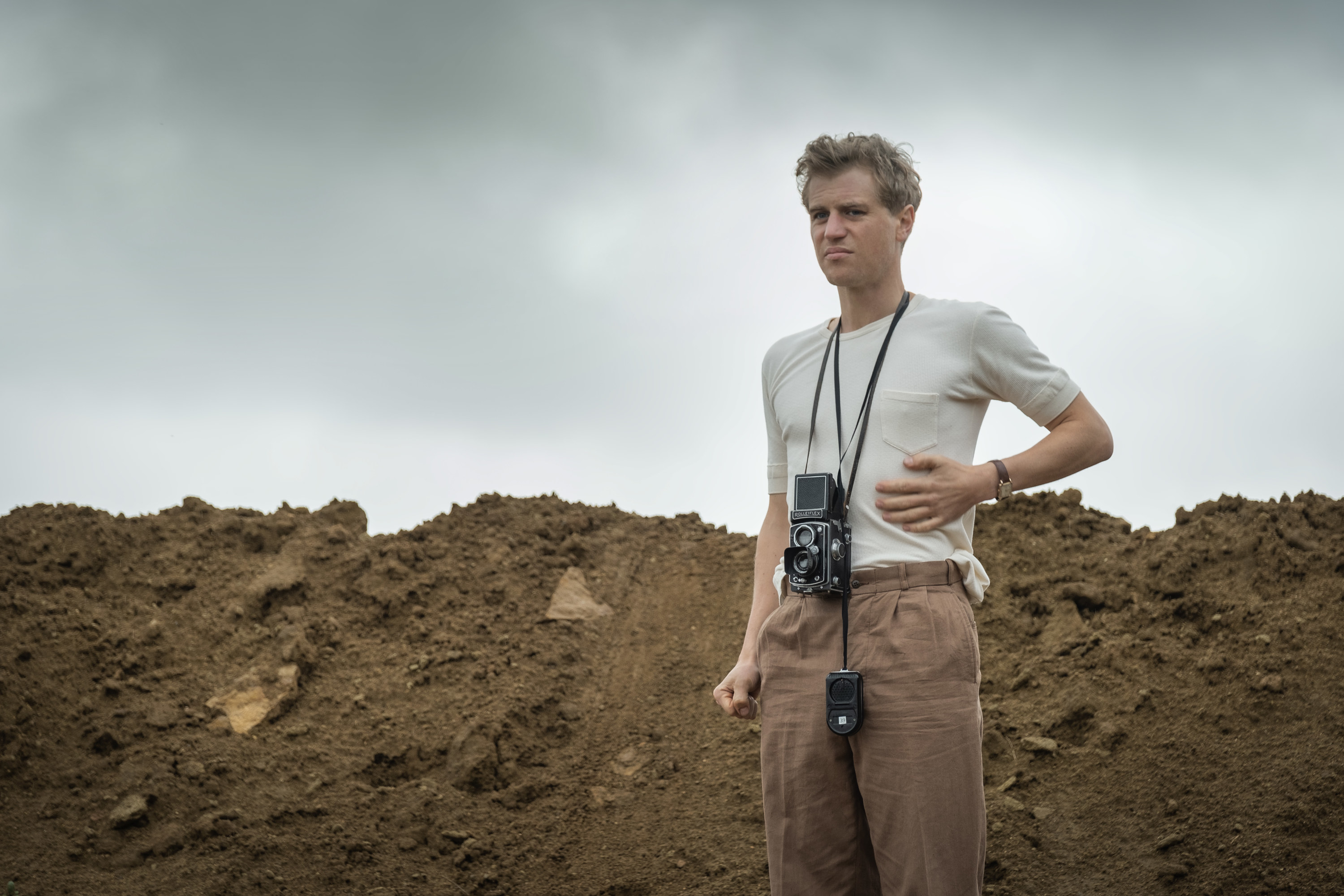 Still from The Dig: Rory Lomax on-site with a camera around his neck