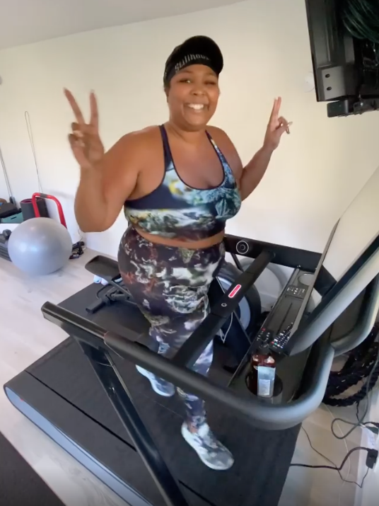 Lizzo gives a peace sign while smiling at the camera