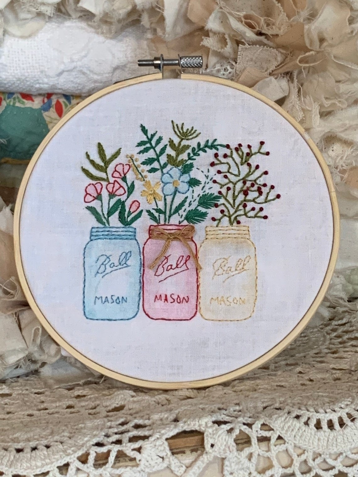 Three mason jars with bundles of flowers in each one