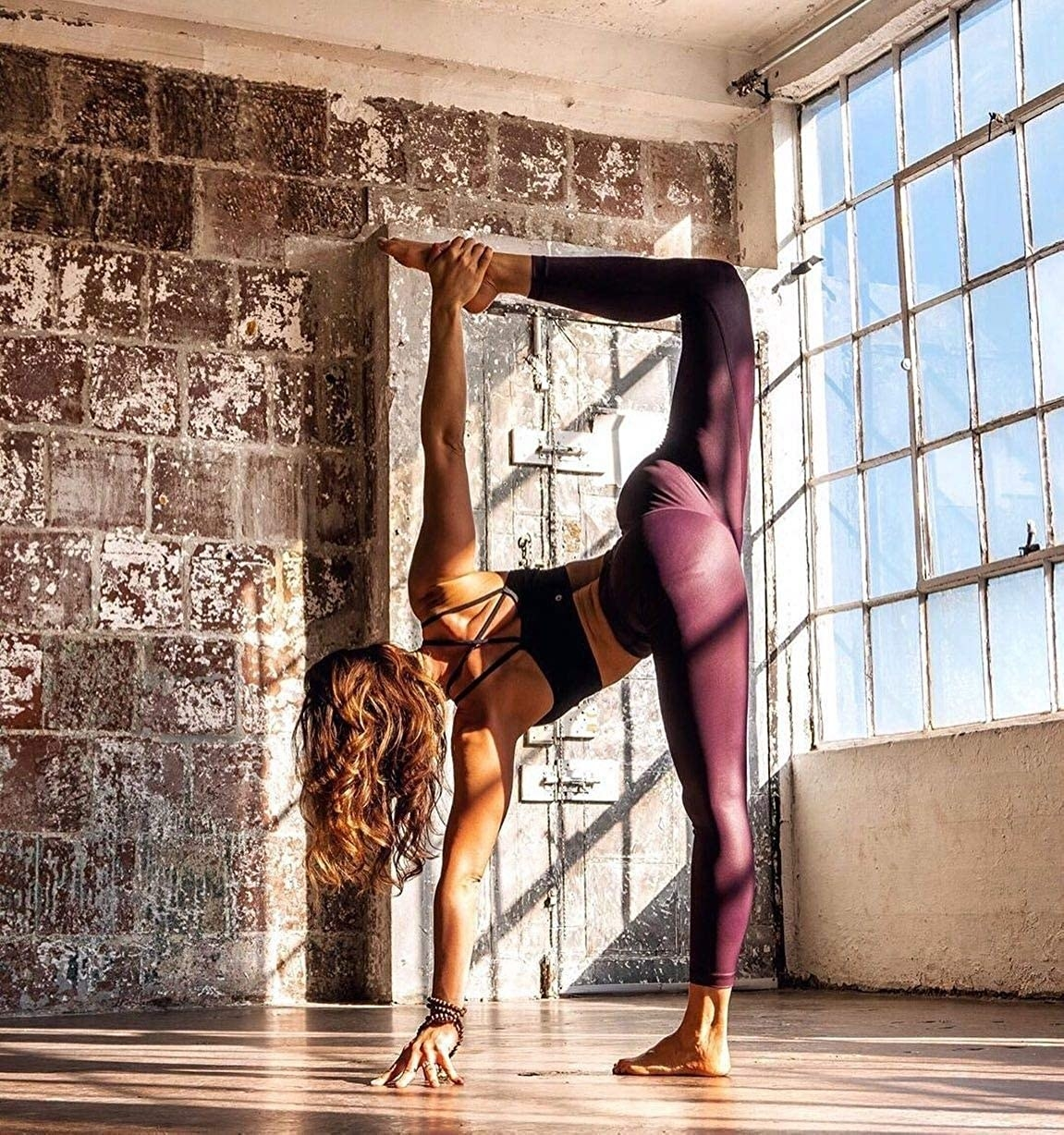 Model does standing yoga pose in mauve high-rise shiny leggings
