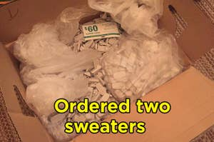 "An open box filled with security tags with ""Ordered two sweaters"" on it"